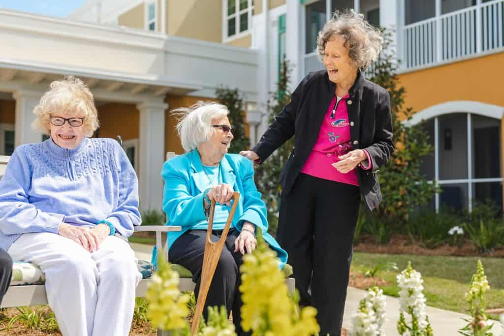 Three senior women socializing in courtyard