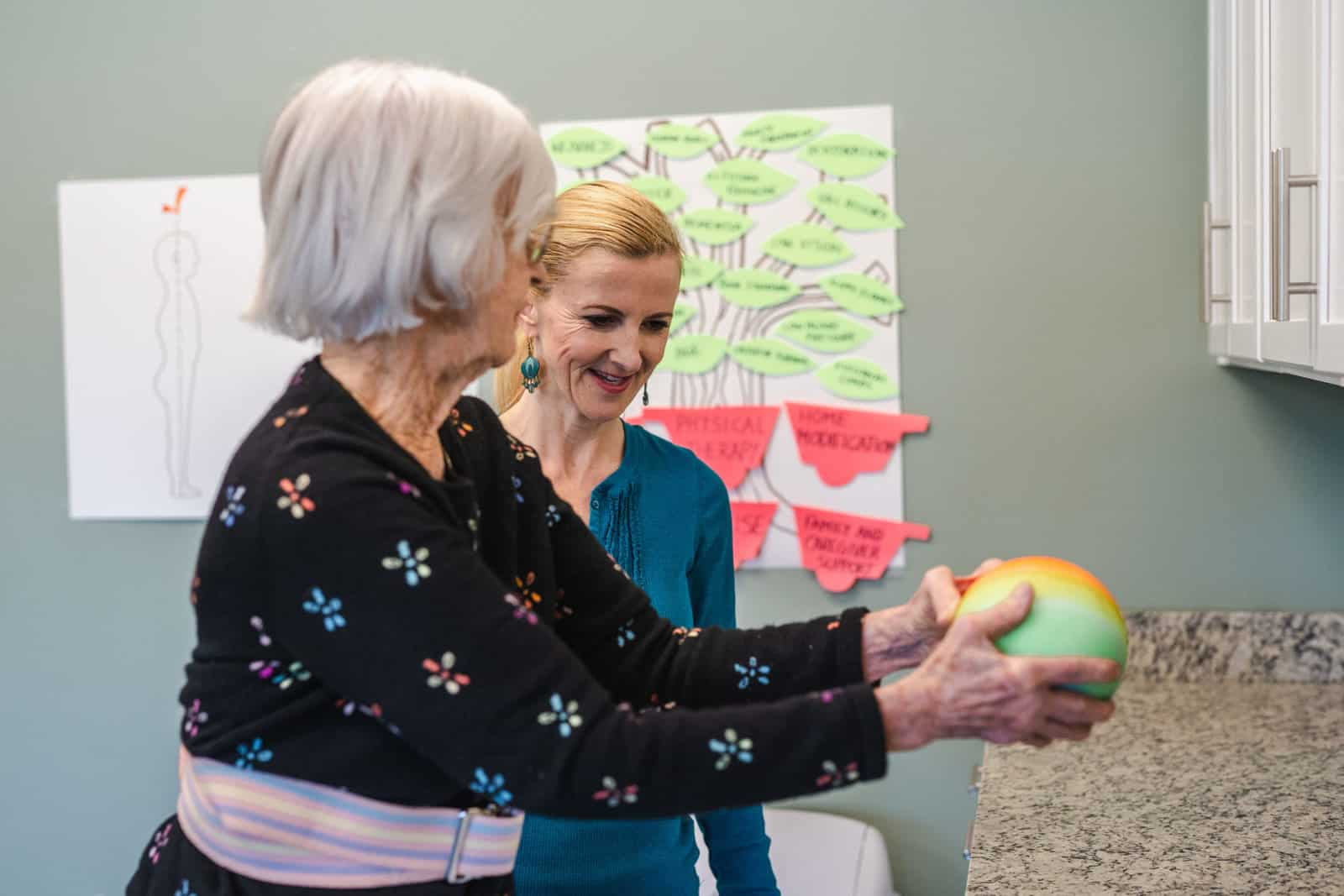 Senior Woman Holding Weighted Ball With Physical Therapist Monitoring