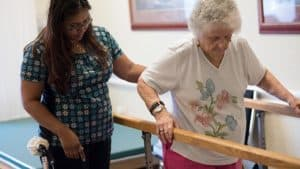 Nurse assisting senior woman with physical therapy