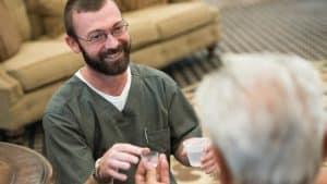 Nurse administering medication to senior man