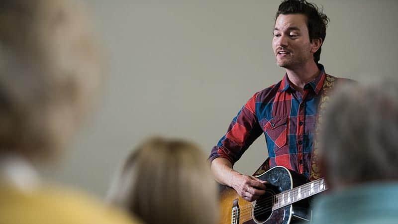 Man playing guitar singing to seniors