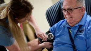 Nurse checking senior man blood pressure