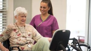Nurse with senior woman using exercise bike