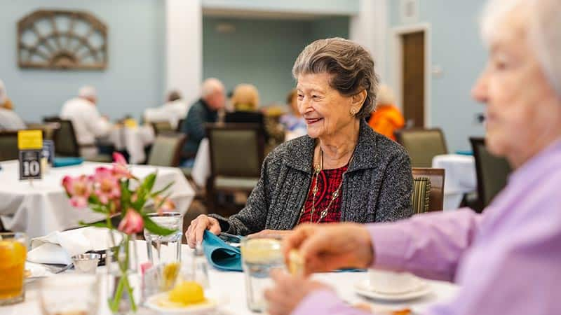 Senior woman seated at dining table smiling
