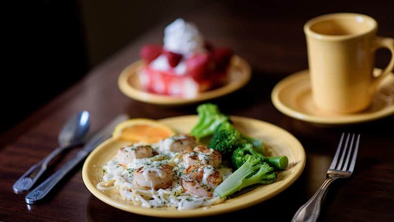 Shrimp pasts with broccoli and pie on yellow plate