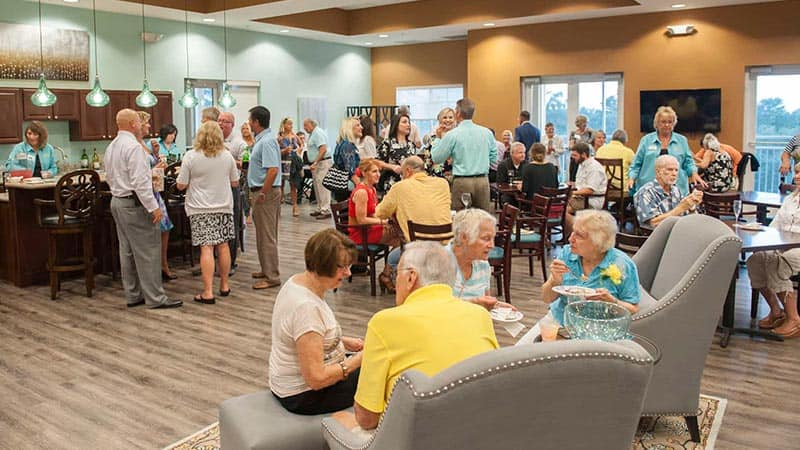 Large group of seniors gathering for daily social hour in the lounge
