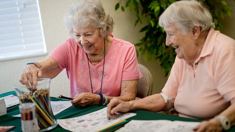 Two senior women coloring together