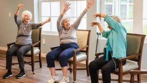 Two senior women stretching during fitness class